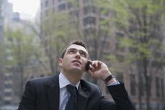 Businessman using mobile phone and looking up Stock Photos