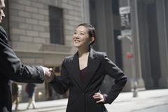 Businesswoman shaking hands with businessman on city street Stock Photos