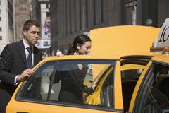 Businessman and businesswoman entering yellow taxi - stock photo