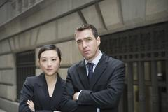 Businessman and businesswoman standing on city street with arms crossed Stock Photos