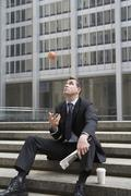Businessman sitting on steps during coffee break and tossing apple in the air - stock photo