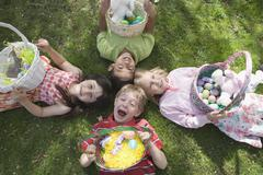 Four children lying down on grass and holding Easter baskets Stock Photos