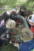 Group of children bobbing for apples at Halloween party - stock photo
