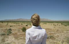 Young woman looking at view of desert Stock Photos