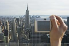 A tourist taking a digital picture of the Empire State Building and New York Stock Photos