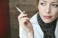 Woman sitting in cafe smoking a cigarette Stock Photos