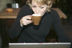 Woman drinking coffee and using computer in cafe Stock Photos
