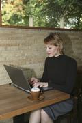 Stock Photo of Woman sitting in cafe and using laptop