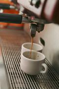 Coffee pouring coffee into two espresso cups Stock Photos