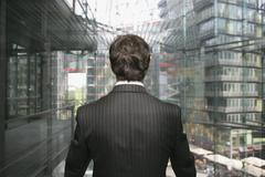 A business man looking out of a glass elevator Stock Photos