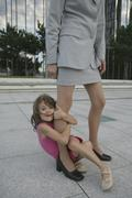 A young girl holding onto a businesswoman's leg Stock Photos