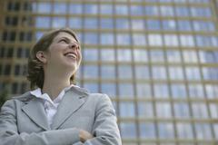 A businesswoman smiling with her arms crossed in front of a glass building Stock Photos