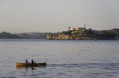 Two people rowing in water with Alcatraz Island in distance, San Francisco, Stock Photos