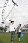 Young couple walking below Millennium Wheel, London, England Stock Photos