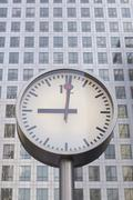 Clock showing 9 o'clock in front of office building Stock Photos