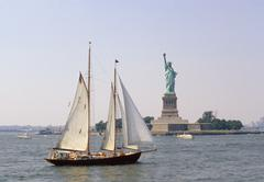 A large sailboat sailing past Ellis Island, New York, USA Stock Photos
