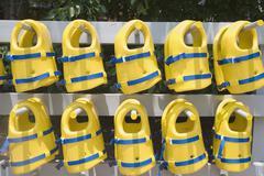 Life jackets arranged on rack Stock Photos