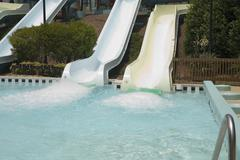 Swimming pool at the bottom of water slide Stock Photos
