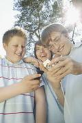 Three teenage boys huddled together using mobile phones - stock photo