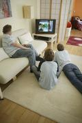 Three teenage boys watching television together Stock Photos