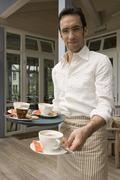 Waiter holding tray with cups of coffee - stock photo