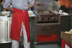 Market vendor cooking sausages Stock Photos