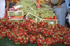 Strawberries and grapes at market stall Stock Photos