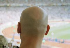 Rear view of man watching soccer game Stock Photos