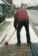Man sweeping snow on sidewalk Stock Photos