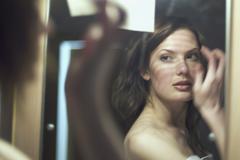 Nuori nainen katsomalla itseään peilistä Kuvituskuvat