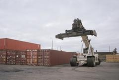 Forklift truck next to cargo containers Stock Photos