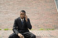 Businessman sitting on bench using mobile phone Stock Photos