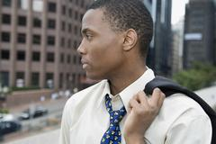 Businessman standing in financial district with jacket over shoulder Stock Photos
