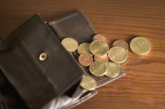 Open wallet with coins spilling onto table Stock Photos
