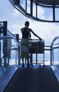 Silhouette of woman pushing luggage trolley Stock Photos
