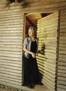 Woman at entrance of log cabin - stock photo