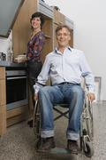 Man sitting in wheelchair and woman standing behind in domestic kitchen - stock photo