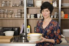Woman holding plates in kitchen Stock Photos