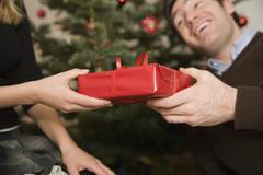 Couple exchanging gift at Christmas Stock Photos