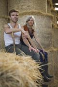 Two workers sitting on bale of hay in a barn Stock Photos