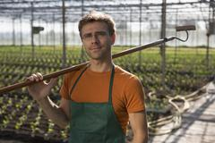 Worker carrying hoe in greenhouse Stock Photos