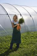 Woman holding bunch of carrots outside of greenhouse Stock Photos