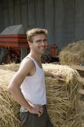 Farm worker resting next to bale of hay and smiling - stock photo