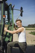 Farm worker climbing into tractor and smiling Stock Photos