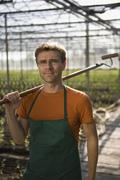 Farm worker in greenhouse carrying hoe - stock photo