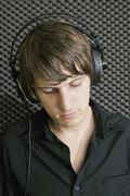 Young man wearing headphones in recording studio - stock photo