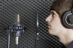 Man in sound booth of recording studio - stock photo