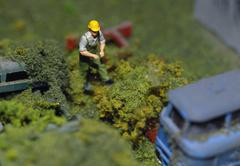 Model of manual worker standing near abandoned cars Stock Photos