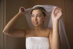 Bride lifting veil over head and looking out window Stock Photos