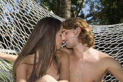 Young couple kissing in hammock Stock Photos